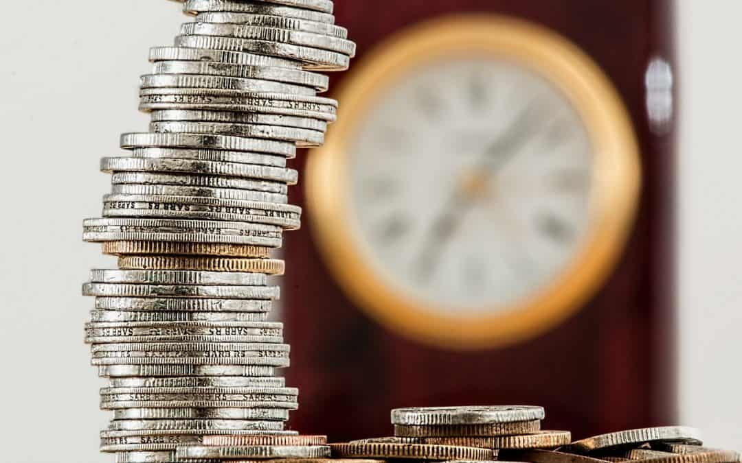 Stack of Coins and Clock Behind