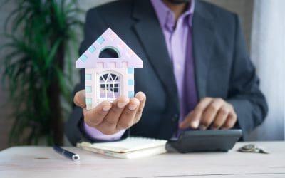 Man Holding Model House Calculator Pen Suit